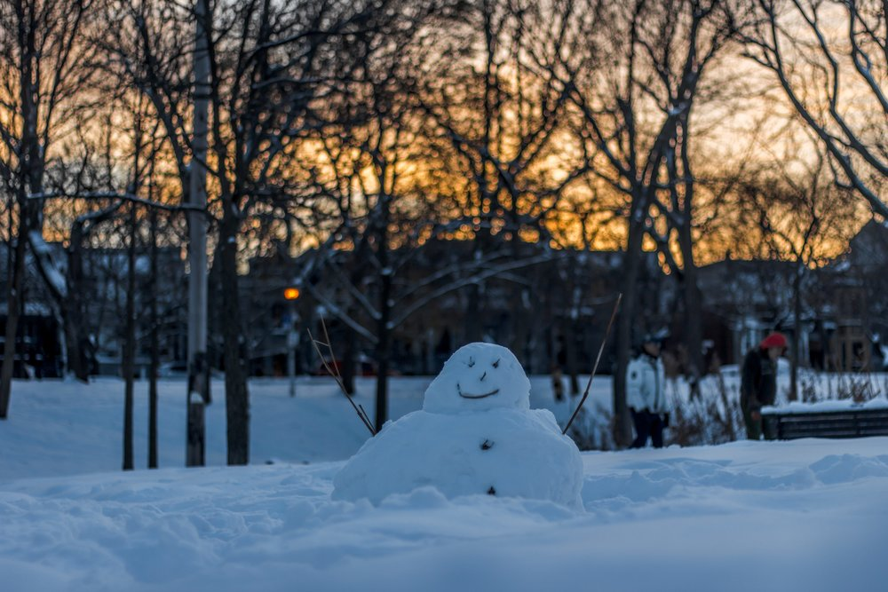Picture of a snowman outside in winter.