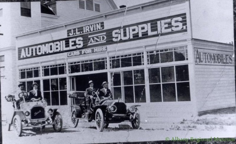 "Irvin's Garage, west side of Broadablin between Third and Fourth, c. 1908. Two cars are parked outside the building, which has signs that read, ""Automobiles and Supplies""; ""Cars for hire""."