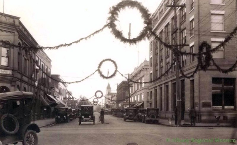 Broadalbin and First Ave at Christmas, showing First National Bank Building, Dentist Dr. Mitchell, and First Christian Church down on 4th and Broadalbin. c. 1934-1938