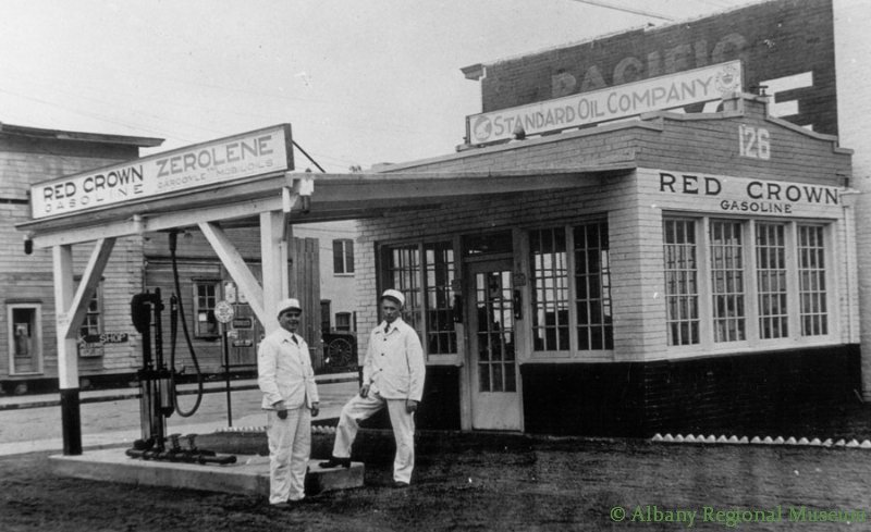 Two men in white uniforms stand beside the single pump at the Red Crown Gas Station, Second & Ellsworth, c. 1912. The Albany Stables can been seen at the far left in this photo.