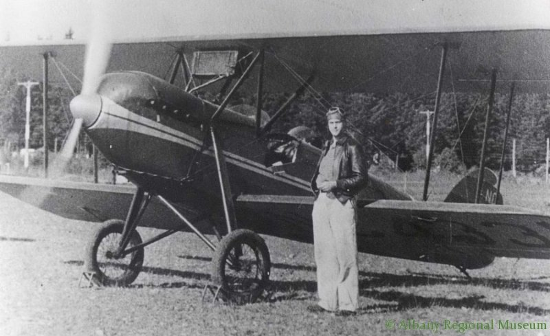 Photo of George Douglas standing in font of his plane, a Waco 10-0x5 single engine, at Albany Airport, 1929. George Douglas (born 1911), one of the early mangers of Albany Airport (Langmack Field) in the 1930s.