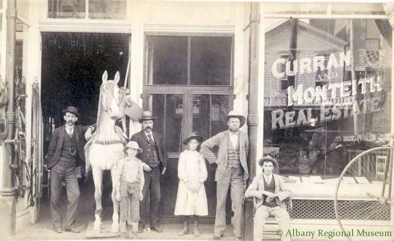 Photographic Print showing office of Curran & Monteith Real Estate office on W. First avenue Albany, Oregon. 8 inches by 10 inches overall, Picture is mounted on cardboard. There is 4 men, 3 standing, one sitting down, 1 young boy and one young lady all in front of doors to Real Estate office and a horse model selling horse equipment. Taken 1889.