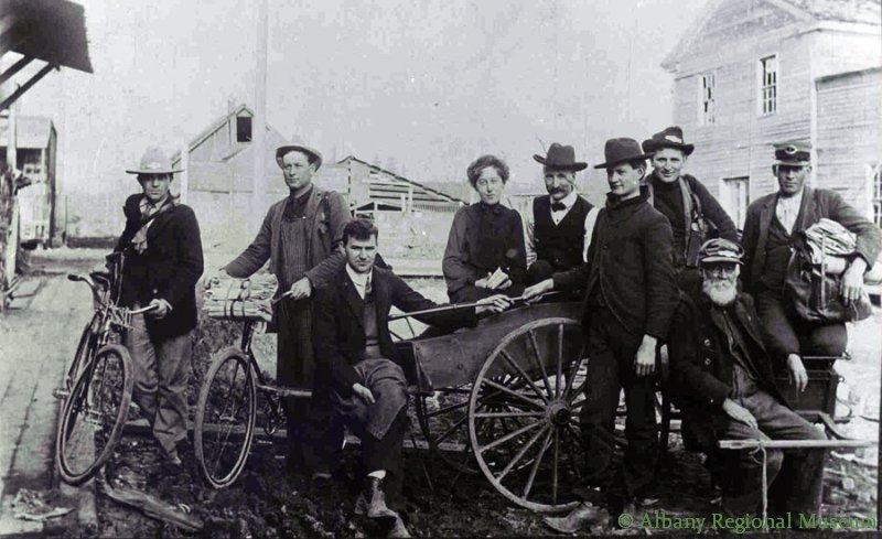Albany postal crew behind post office. Walt Worrell is at right of the lady. Monteith store is at right on Water and Ferry. c. 1905.