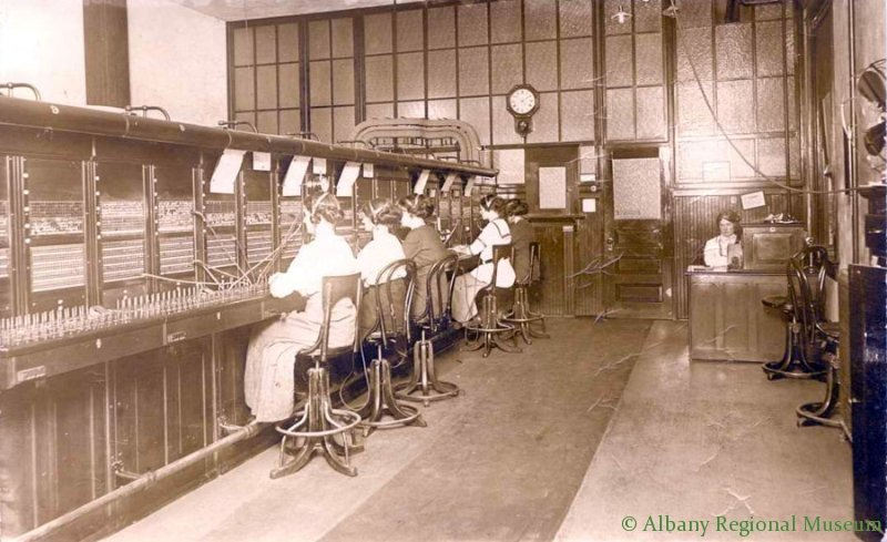 Photographic Print on Postal card of Albany Bell telephone office when it first moved into the Burggraf Building on 2nd Ave in the 100 West block. Shows 5 women at telephone switchboard and 1 woman, Maybe the supervisor, seated at desk facing camera. Has names on back but are hard to read. c. 1900.