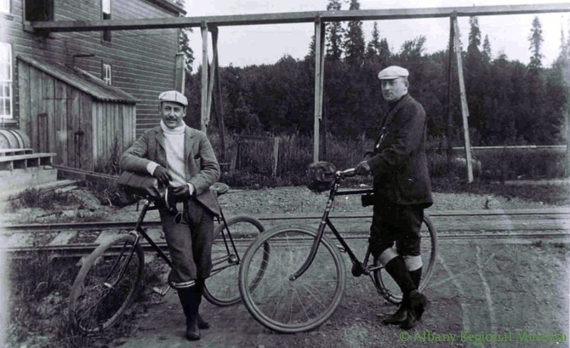 Robert Albert Bertram Veal and Percy R. Kelly at Water Ave. plant of Veal Chair Factory and their bikes. Kelly became a Circuit Court Judge and later a Justice on the Oregon Supreme Court. c. 1900.