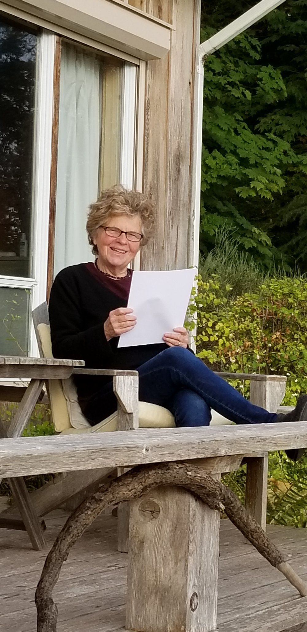 Arleen reading a local writer's submission on the porch.