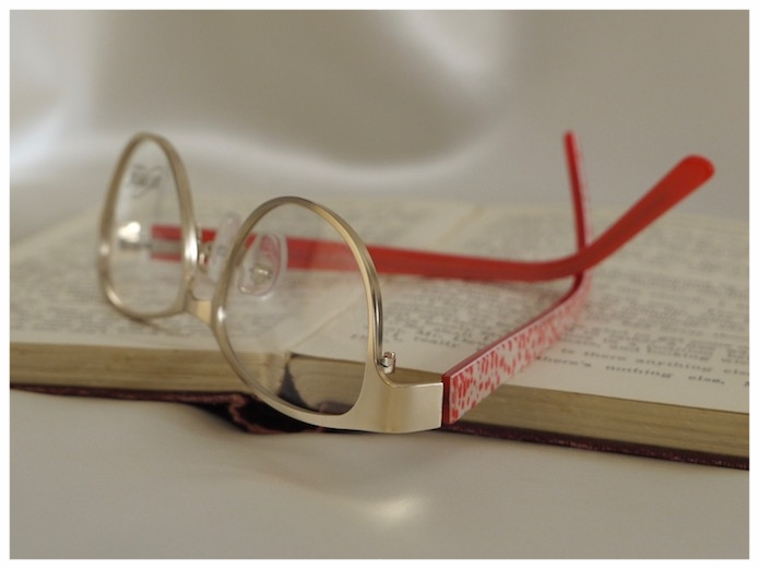 pair of reading glasses with brushed gold frame and coral coloured temples