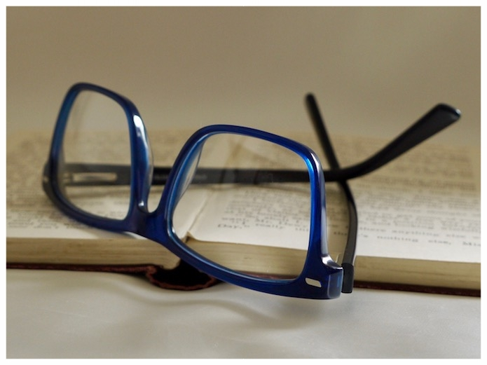 pair of blue spectacles with glass reading lenses.