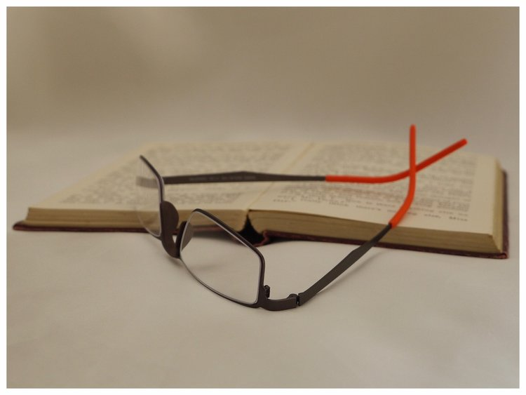 pair of dark grey office spectacles with bright orange temple tips