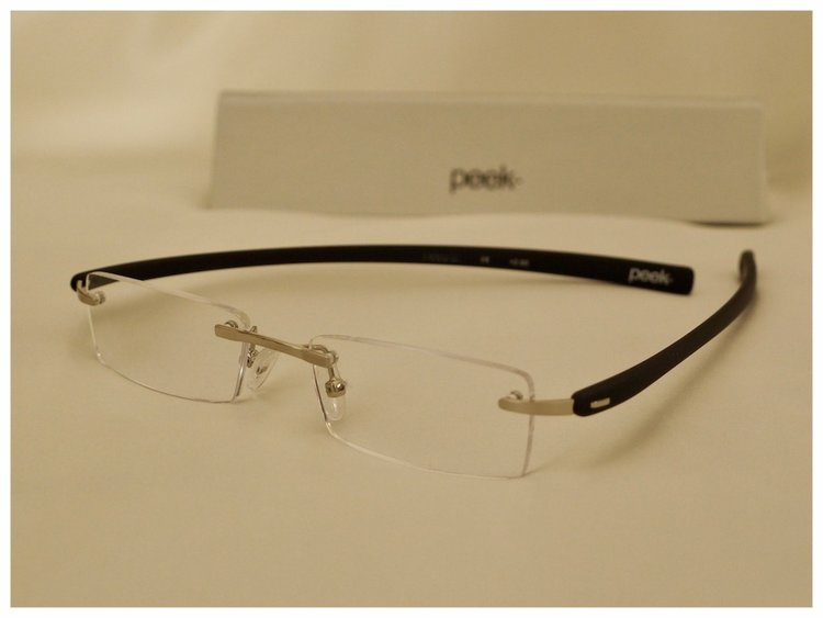 pair of rimless reading glasses with silver coloured nose-bridge.