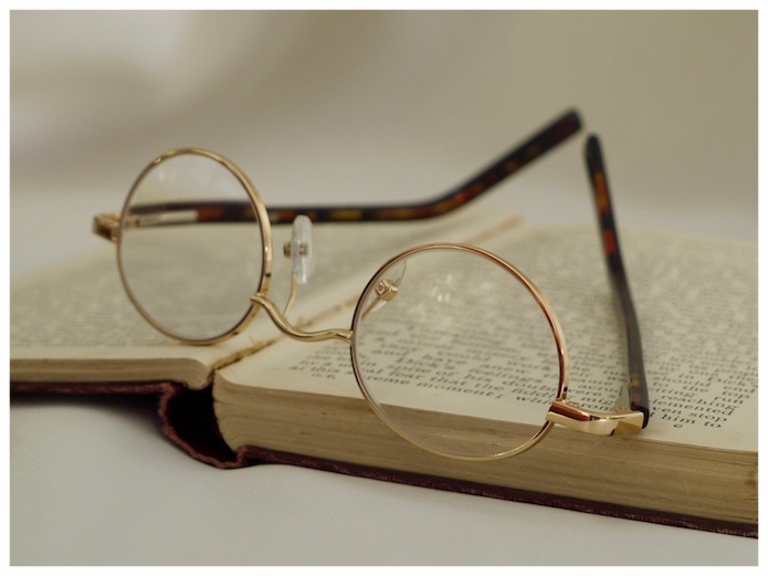pair of gold coloured, oval-shaped reading glasses.