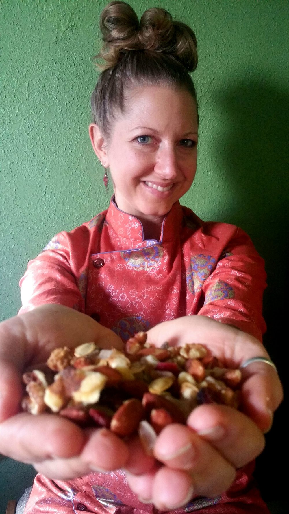 A photo of Lauren. She has dark hair in a bun, and she's smiling at the camera. She's holding nuts and seeds in her cupped palms, and her hands are close to the camera and slightly out of focus.