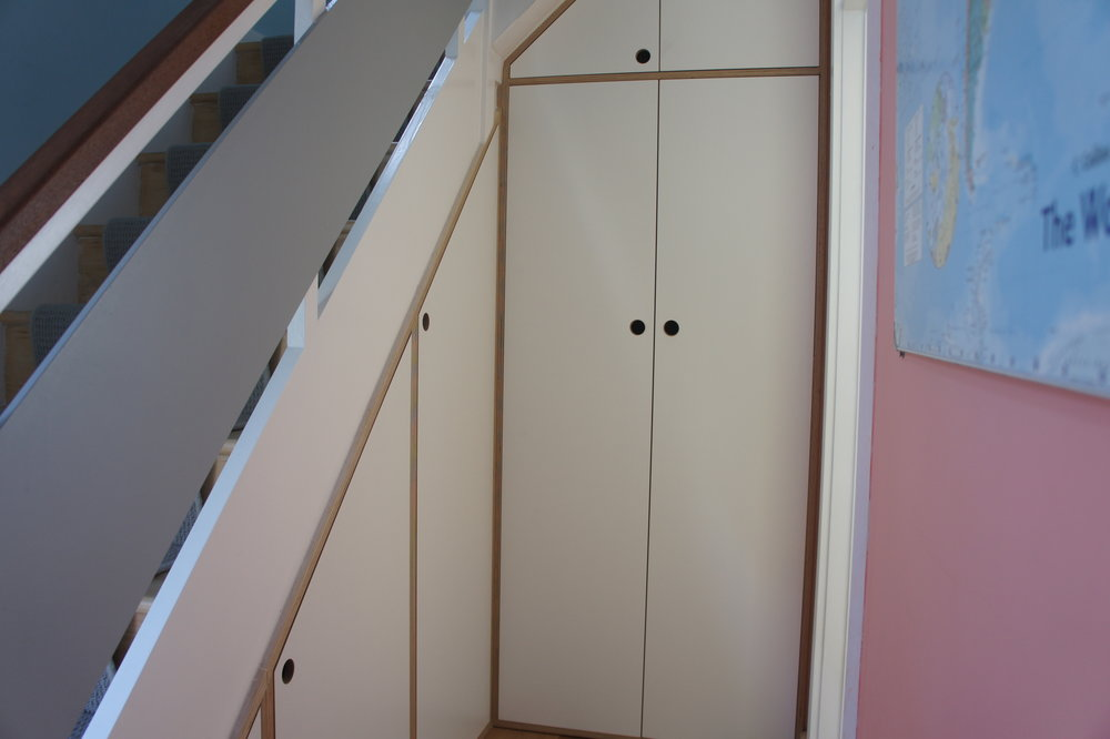 unders-stairs storage in melamine faced plywood with cut out finger pull detail