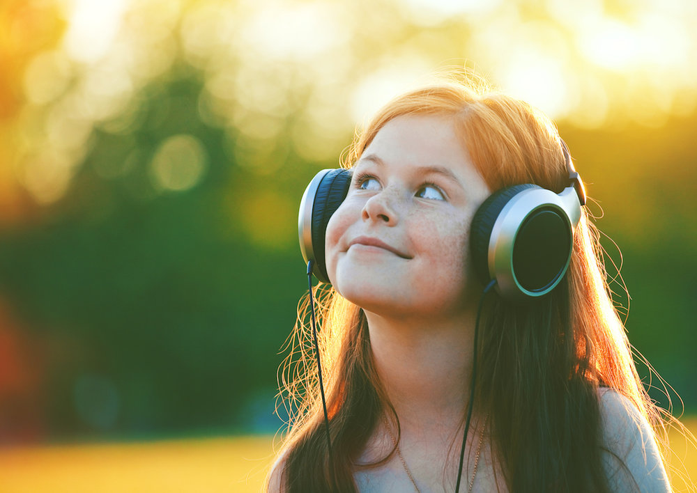 redhead girl with headphones listening to music. space for text