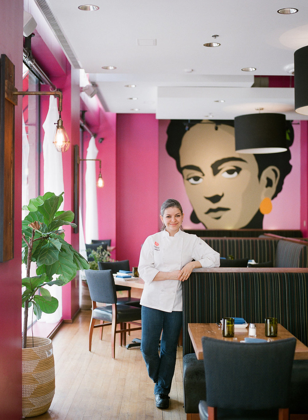 Picture of Maria Oseguera, business owner of Maya on Grace. Maria is leaning against with restaurant booth with the image of Frida Kahlo.