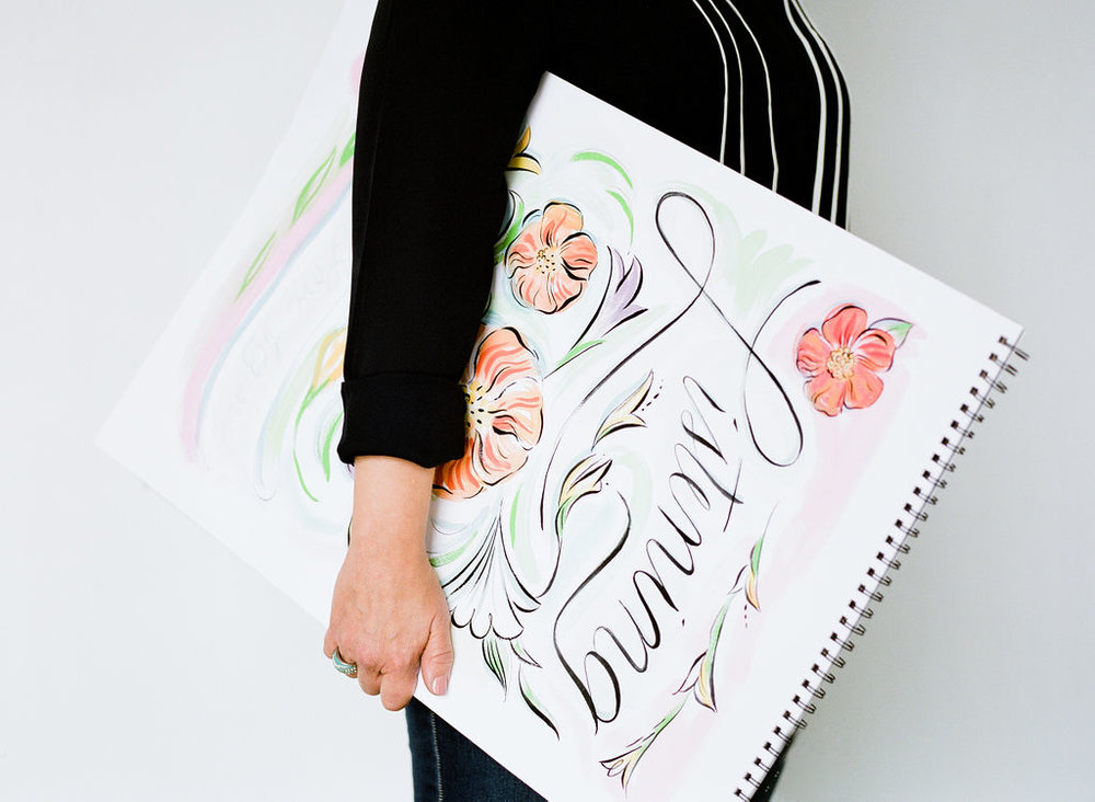 Laura Marr holding a large drawing canvas. Laura is wearing a black shirt and pant. Illustrative rending is of a colorful flower imagery.