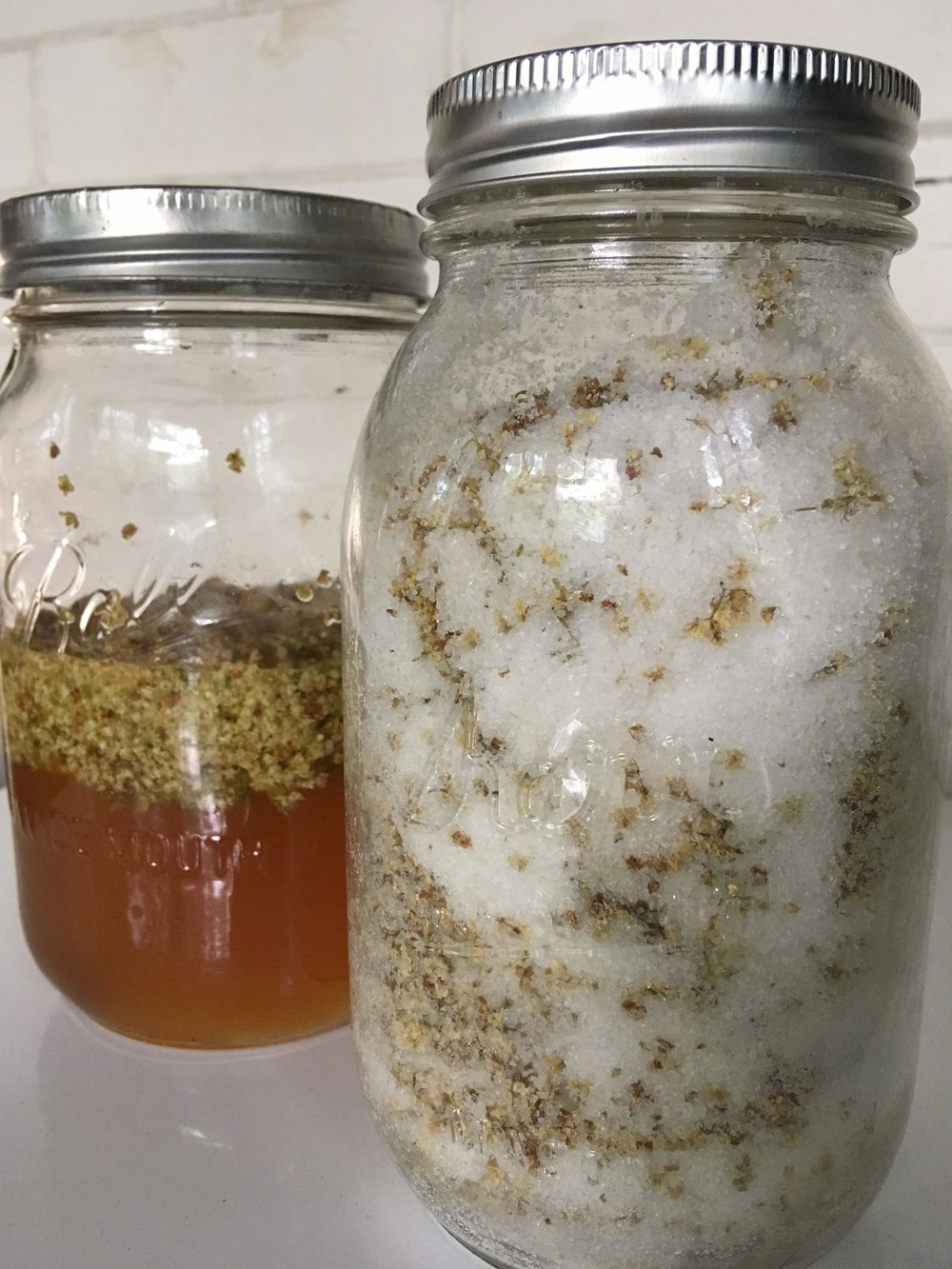 Infusing honey (left) and salt (right) with elderflowers.