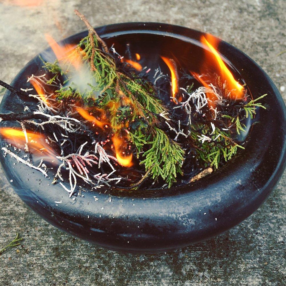 Burning dried juniper twigs for culinary ash.