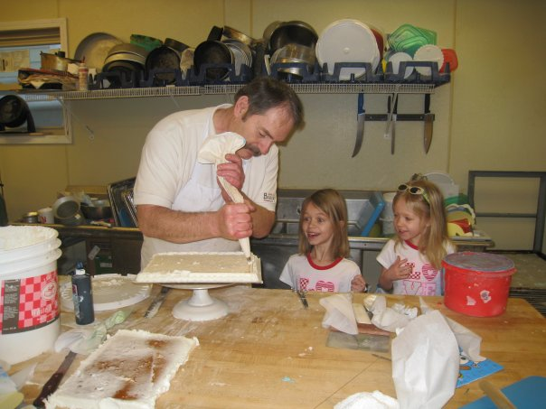 My Dad teaching his granddaughters how to ice a cake, 2007.