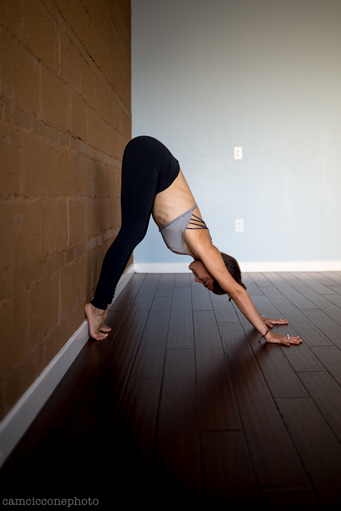 Stage Two - Keep the prior activations and lift the knees away from the floor and pike the hips up towards the wall. Spread the upper back wide by breathing deeply into the shoulder blades and hugging the upper arm bones together to stabilize the shoulders and clear some space around the neck.