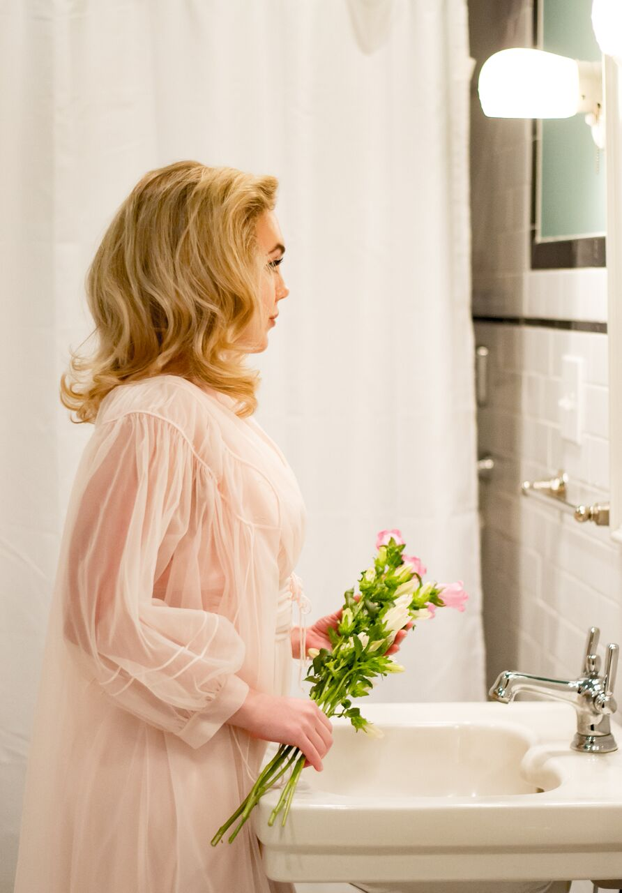 pink holding flowers looking in mirror side view.jpeg