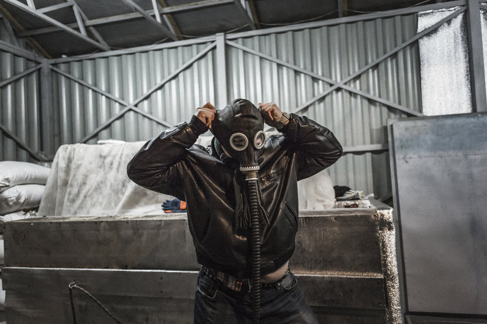 Sergiev Posad, Moscow region, Russian federation, November 2017. One of Kriorus' technicians is about to get into the cooling chamber before the immersion into liquid nitrogen. In the cooling chamber the bodies are covered with dry ice in order to homogeneously drop body temperature to -78°C. The use of the mask is mandatory, because the carbon dioxide vapours produced by sublimation can cause asphyxia.
