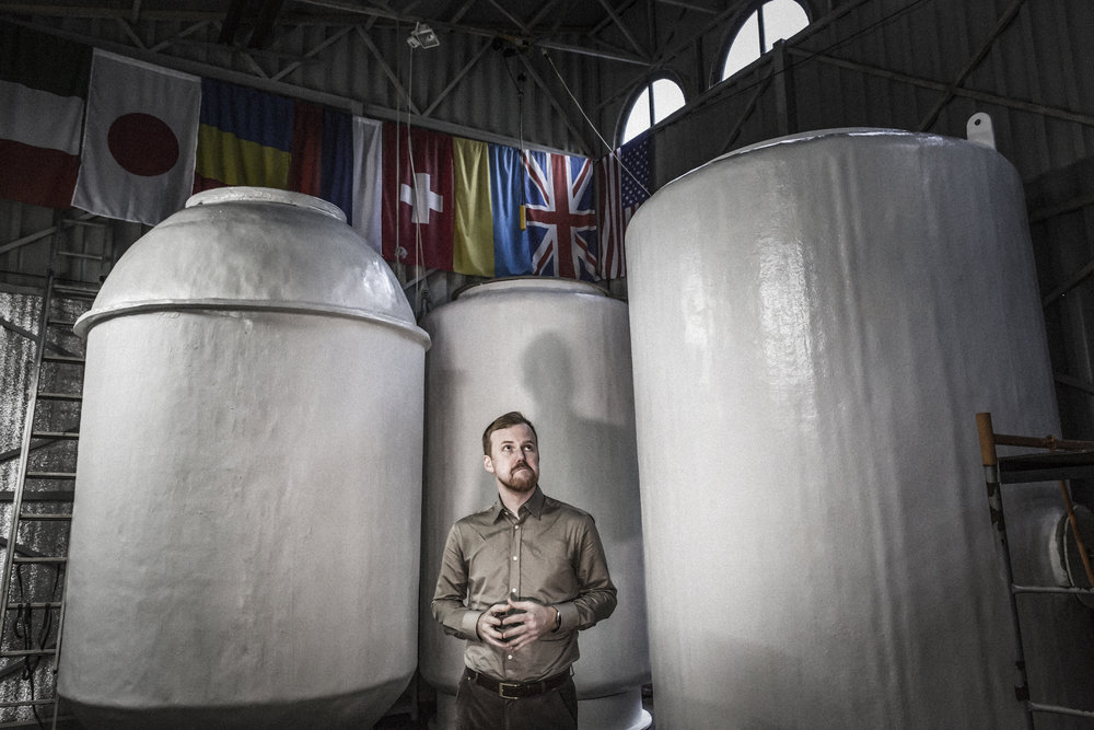 """ergiev Posad, Moscow region, Russian federation, June 2017. Danila Medvedev, member of the Governing Council of the Russian Transhumanism Movement and Kriorus founder in May 2005. In the background the three dewars in which the patients' bodies are cryopreserved. The three """"Pots"""" are classified as Anabiosis 1, 2 and 3, and each of them can contain up to 8 bodies."""