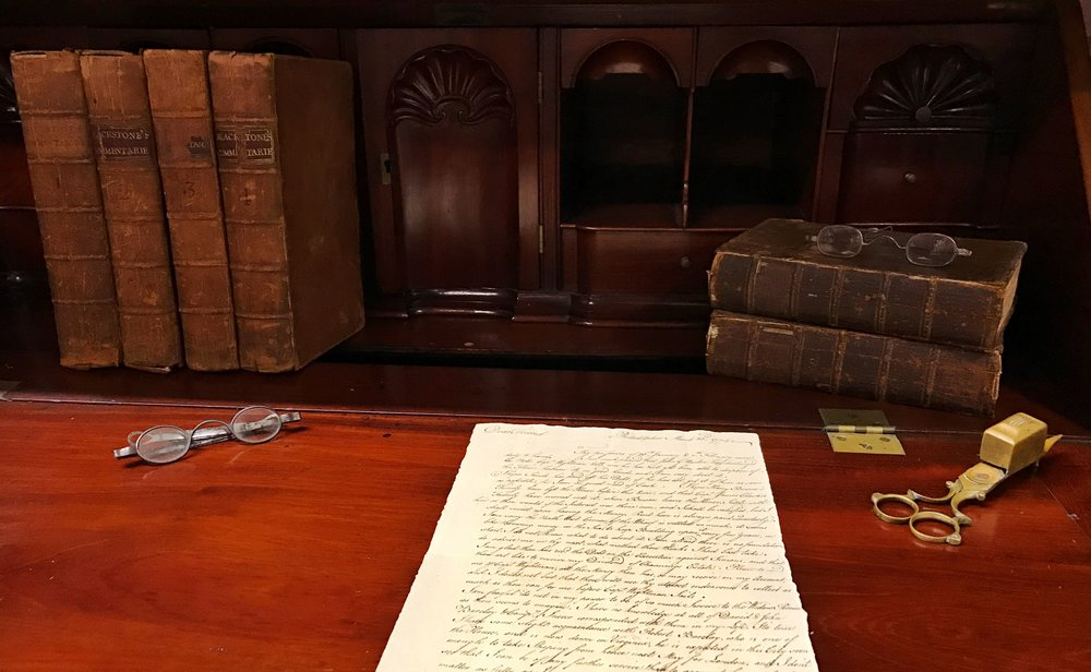 William Ellery's desk with two reading glasses, wick trimmer, Ellery's four-volume set of Blackstone's Commentaries (1771-1772), Ellery's two-volume set of Baron de Montesquieu's Spirit of the Laws (1752), and a letter from William Redwood to William Ellery dated March 23, 1774; Newport Historical Society collections. With permission from NHS.