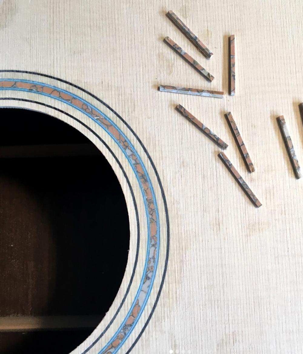 Rosette ring, top perimeter and peghead logo interior made of jasper stone.