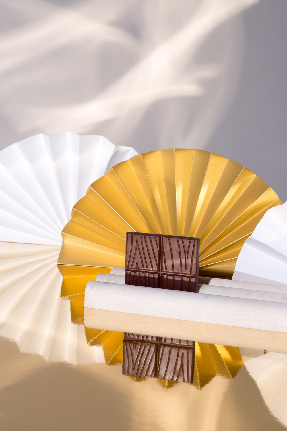 Paper Trails — Serra + Woodblock Chocolate edibles in a paper sculptures universe.