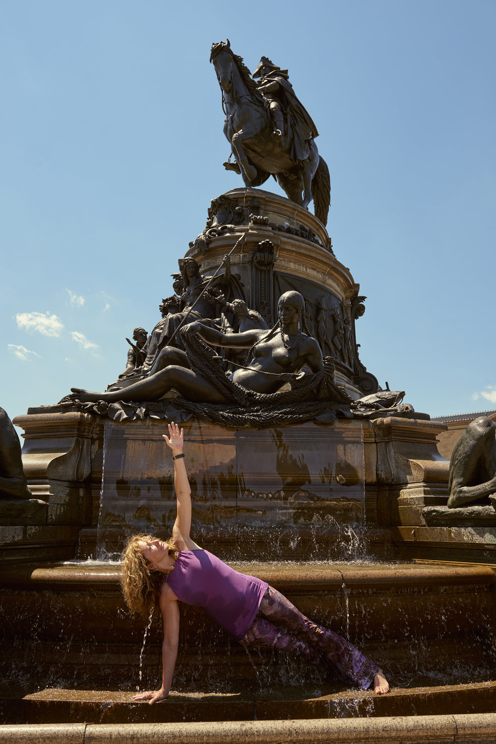 Rosa practicing yoga in an Eakin's Oval fountain in front of the Philadelphia Art Museum.