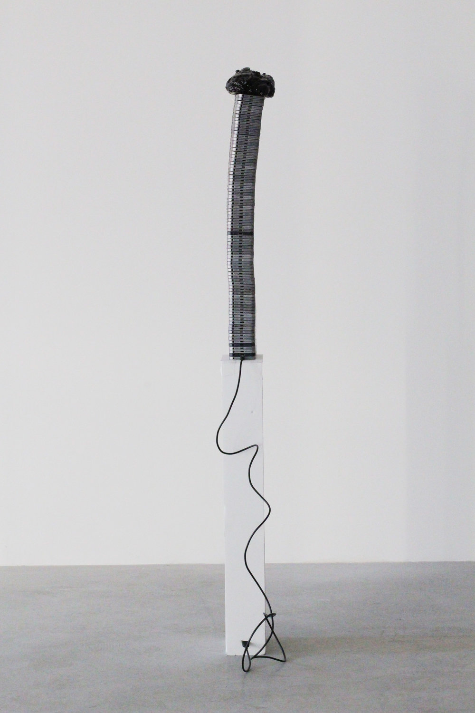 Untitled (Too Thick),  2018 Aluminum phone casings, silicone, polyurethane, asphalt, wood, Lightning to USB cord (photo courtesy HOUSING, Brooklyn, NY)