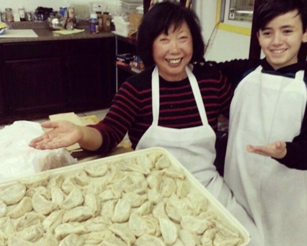 Ms. Kim teaching her secret, family-dumpling recipe to her grandson