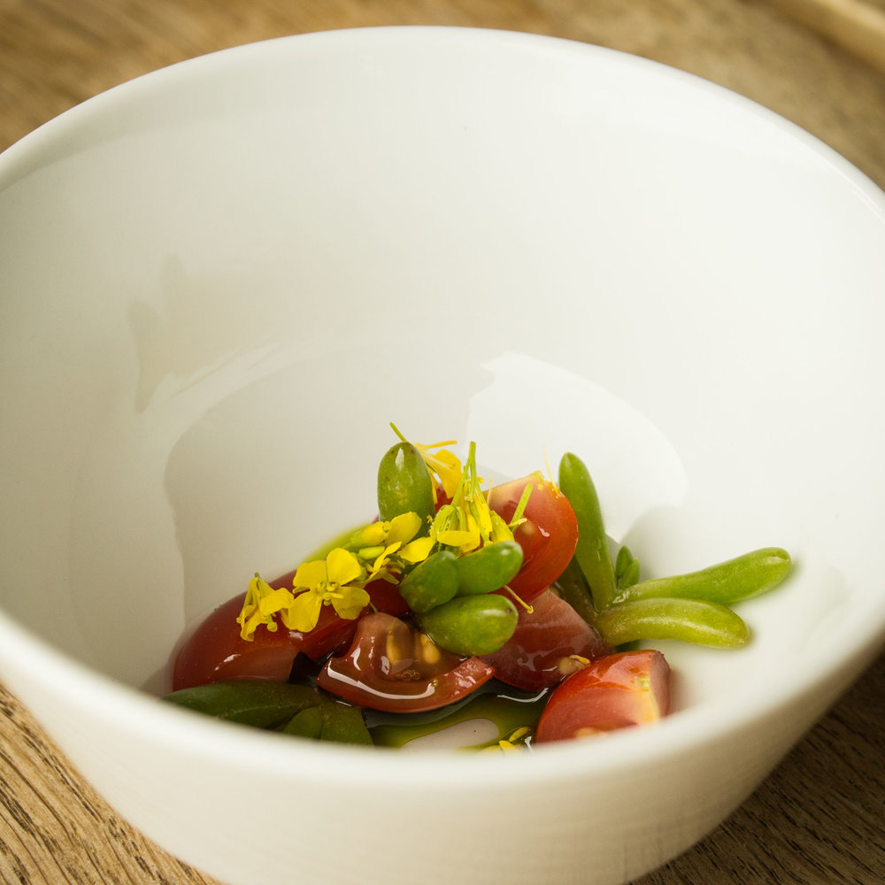 Tomato consommé with salty fingers and mizuna flowers