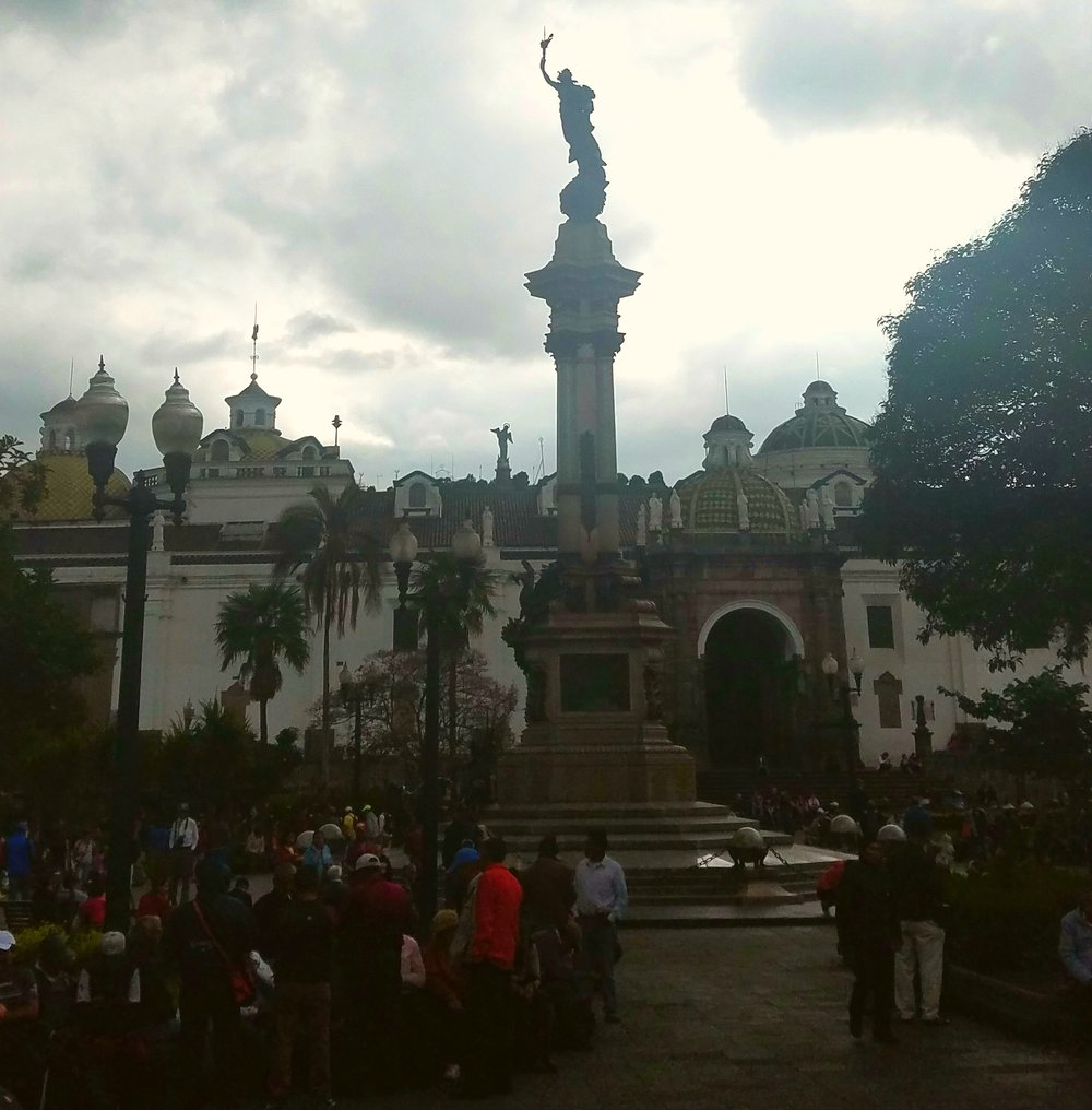 One of many statues in the Plaza Grande; the Vigen de Panecillo looms in the background.