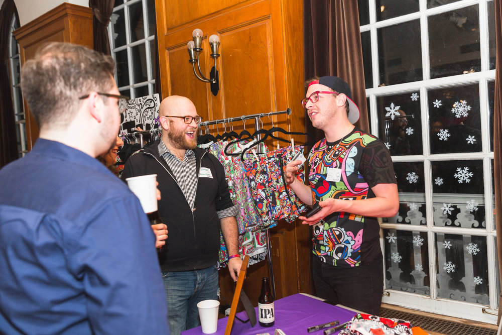 Tyler Wallach aka the 1988 lovechild of Keith Haring and Lisa Frank conversing with Moon Jam guests. Tyler live-painted an canvas during the event, featured a pop-up shop, created the outline of the Community Canvas and custom-painted Moonshot tote bags for the raffle.