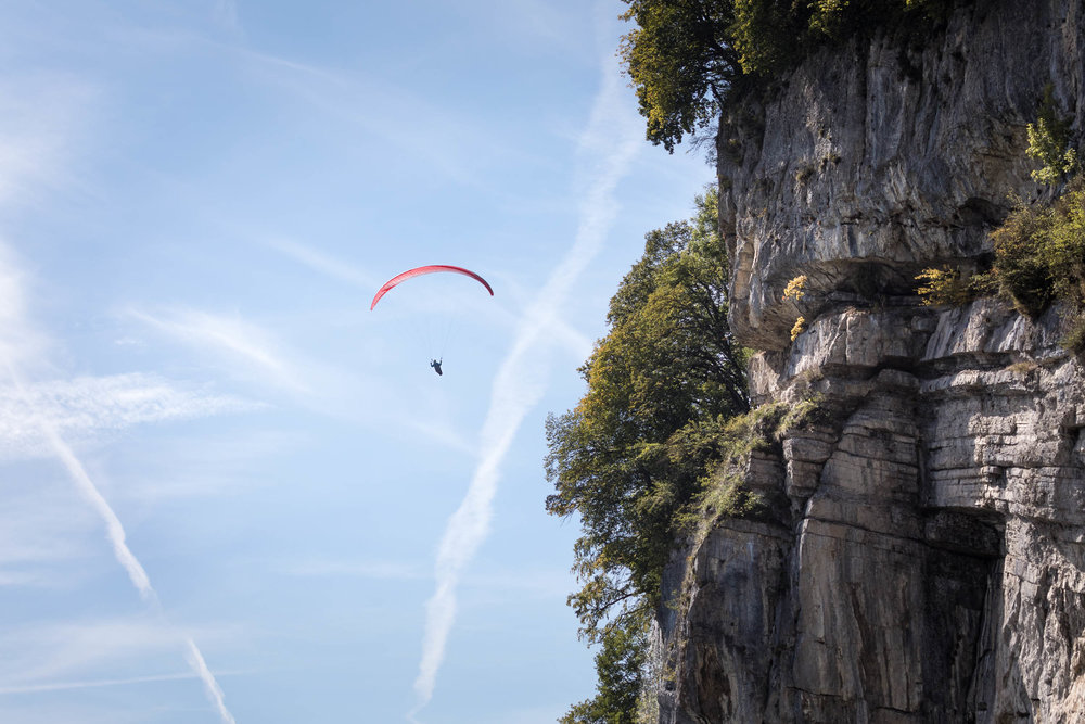 A paraglider enjoys a close-up view of the cliffs