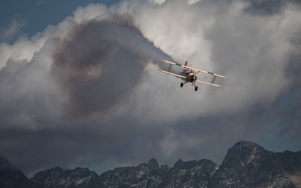 An old bi-plane comes roaring in form the clouds