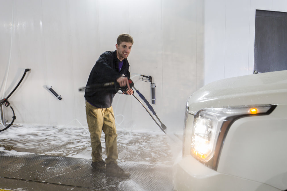 Employee Washing Car With Pressure Hose In Wausau, WI
