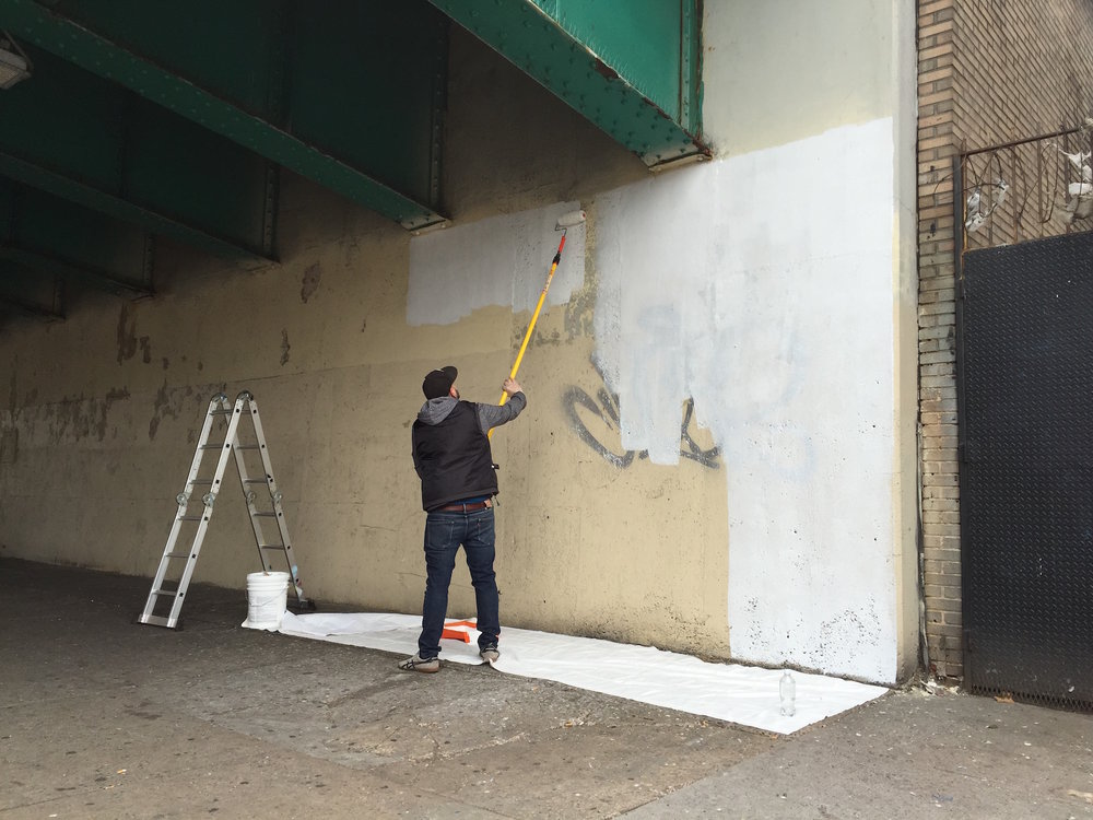 "Artist Miguel Del Real prepares the wall along 4th Ave for the mural ""Intersections,"" funded by NYC Department of Transportation's Art Program (2015)."