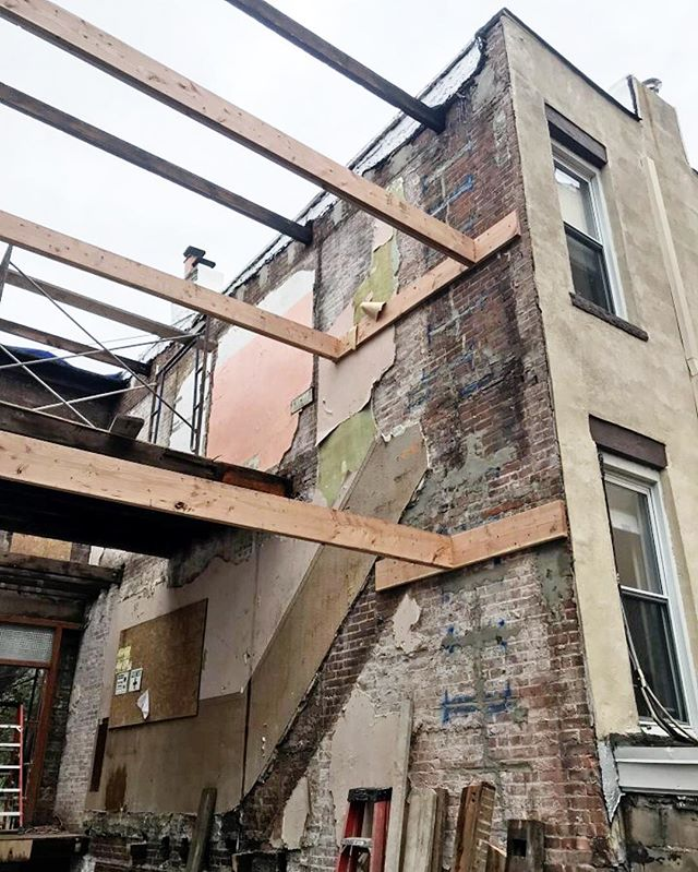 "When we demoed our 7th street project, we  had to take down the side walls and frame an entirely new building within to ensure it was structurally sound. These beams you see are temporary lateral stabilization to make sure nothing moves in the meantime. As our framers create each new floor, they'll remove them one by one until the new structure is complete. A whole new level of being ""close"" with your neighbors 😅👋🏼"