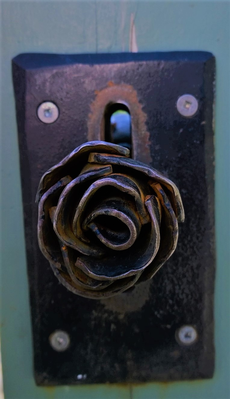 The door handle that allows you entry into a rose garden resembles a rose flower.