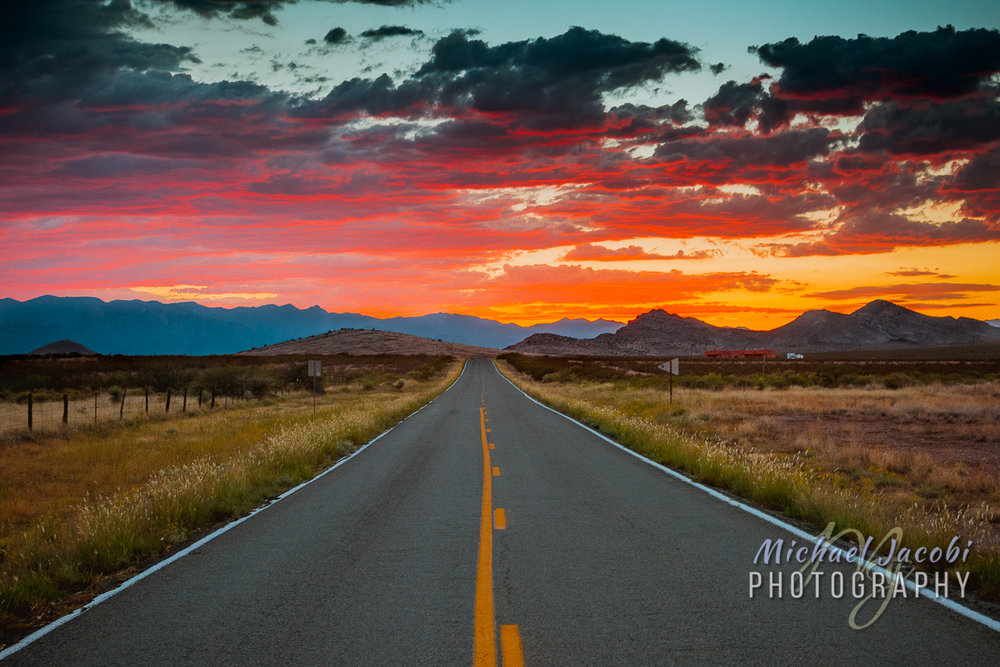 New Mexico State Highway 9 heads west into the sunset from Animas towards Antelope Pass (Animas Mountains) with Arizona's Chiricahua Mountains in the distance.