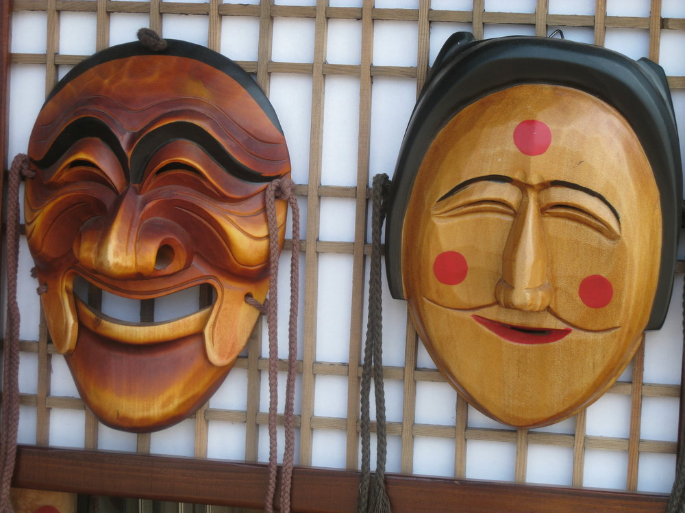 Two Korean  Hahoetal  masks displaying noticeably different smiles (left: the powerful, domineering aristocrat Yangban; right: the affiliative, flirtatious Pune).