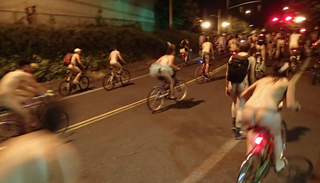 Naked riders climb through a Northeast Portland neighborhood on the 7-mile route. (Christina Cooke)
