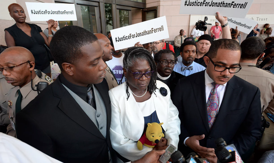 'We're not about violence,' said Jonathan Ferrell's younger brother Willie, standing beside his mother Georgia and family attorney Chris Chestnut,right, outside the courthouse. Photograph: T Ortega Gaines/AP