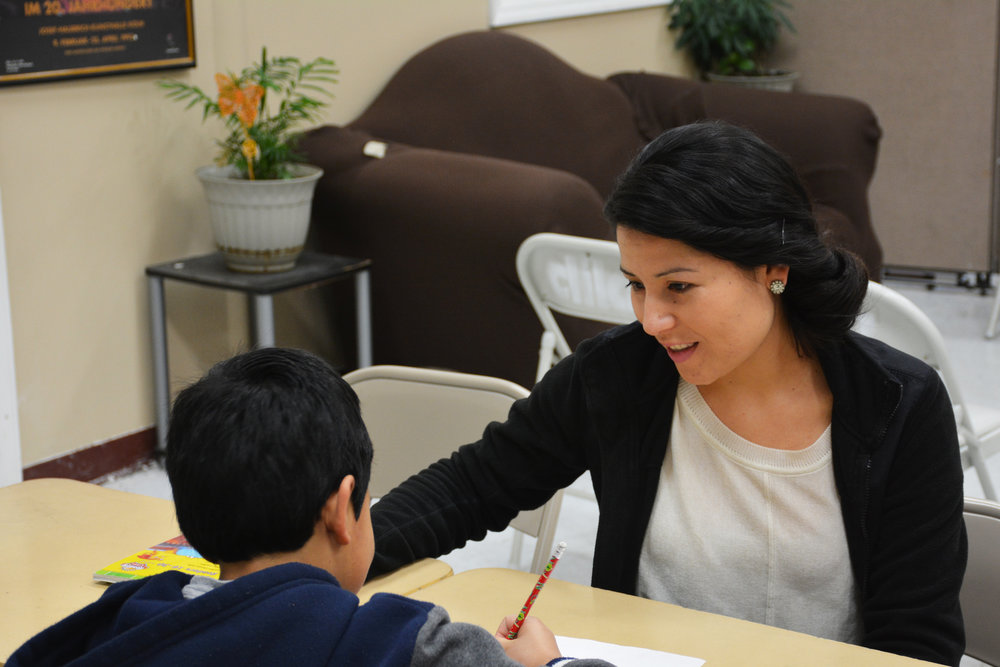 Sujey Guzman helps a local student with his homework. Guzman says many children from Dalton, Georgia's Hispanic community worry what will happen to their parents under the Trump administration.
