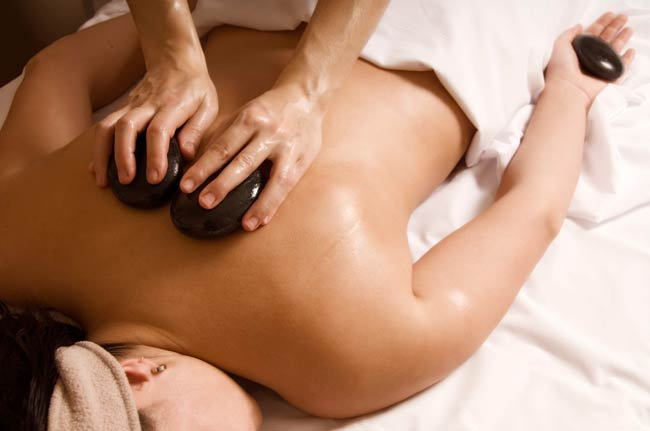 Massage therapist using hot stones on a client's back.