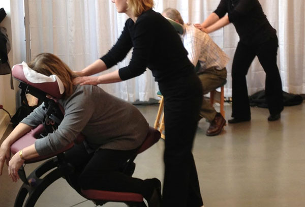 Massage therapist's providing chair massage for an office event.