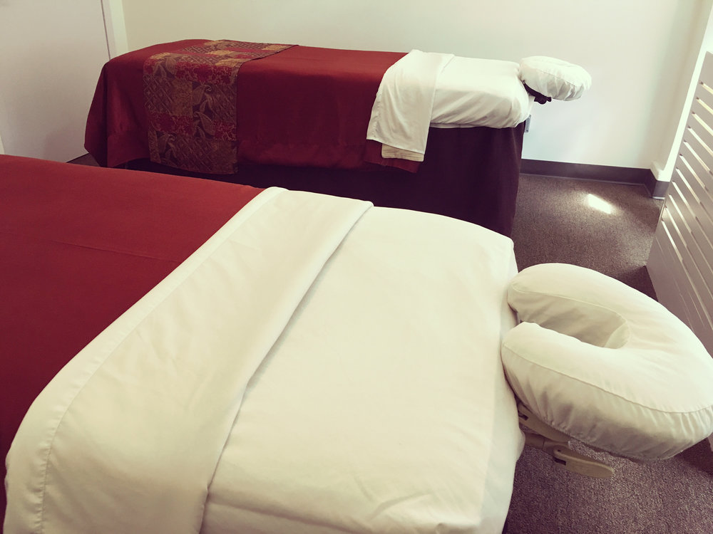 Spacious treatment room with side-by-side tables for a couples massage.